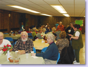 people at tables for pancake supper